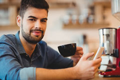 Young man holding mobile phone and coffee cup Stock Image