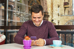 Young man holding a mobile phone and smiling Royalty Free Stock Images