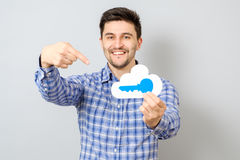 Young man holding model of cloud with blue key. Cloud computing, technology, connectivity concept Royalty Free Stock Photos