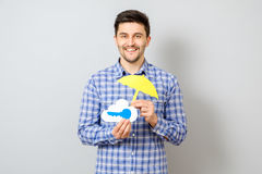 Young man holding model of cloud with blue key and yellow umbrel. La. Cloud computing, technology, connectivity concept Royalty Free Stock Photography