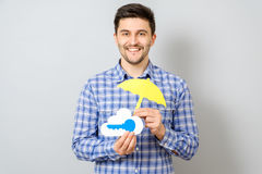 Young man holding model of cloud with blue key and yellow umbrel. La. Cloud computing, technology, connectivity concept Stock Photography