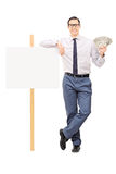 Young man holding money by a blank banner Royalty Free Stock Image