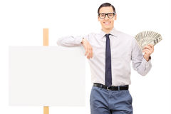 Young man holding money by a blank banner. Isolated on white background Royalty Free Stock Photography