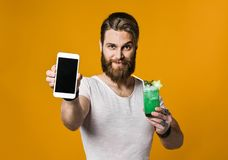 Young man holding a multicolored cocktail royalty free stock photos