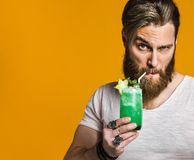 Young man holding a multicolored cocktail stock images