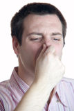 Young man holding nose. Young man holding his nose closed with fingers, like something smells stock photography