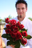 Young Man Holding out Roses. Young man holding out red roses, model out of focus, focus on the roses Stock Image