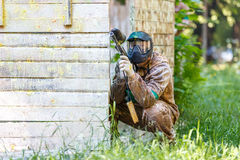 Young man holding paintball marker with yellow paint splashes Royalty Free Stock Images