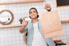 Young man holding paper bag and blank business card while standing in store and smiling at camera Stock Photography