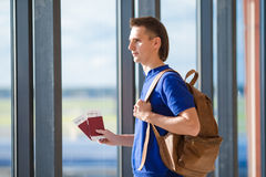 Young man holding passports and boarding pass at Royalty Free Stock Images
