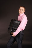Young man holding a pc black background with soft shadow Royalty Free Stock Image