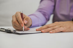 Young man holding a pencil, writing on a paper in the diary.  stock photography