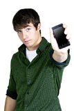 A young man holding a phone. A young man holds a phone towards the camera stock photos