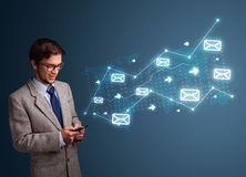 Young man holding a phone with arrows and message icons Royalty Free Stock Photo
