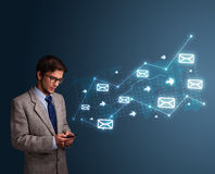 Young man holding a phone with arrows and message icons. Attractive young man standing and holding a phone with arrows and message icons Stock Photo