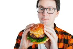 Young man holding a piece of hamburger. Student eats fast food. Burger is not helpful food. Very hungry guy looks at the burger royalty free stock photos
