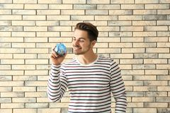 Young man holding piggy bank on brick background. Savings money concept stock image