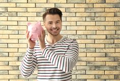 Young man holding piggy bank on brick background. Savings money concept royalty free stock photo