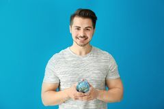 Young man holding piggy bank on color background. Savings money concept stock photos