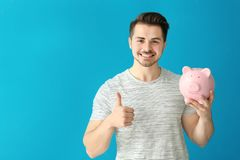Young man holding piggy bank on color background. Savings money concept royalty free stock photography