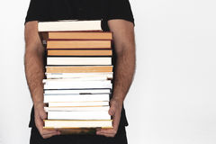 Young man holding a pile of books against a white wall. Empty copy space Royalty Free Stock Image