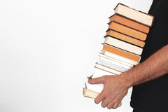 Young man holding a pile of books against a white wall. Empty copy space Royalty Free Stock Images