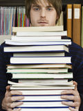 Young Man Holding Pile Of Books Royalty Free Stock Image