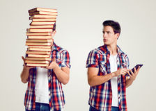 Young man holding a pile of books and tablet Royalty Free Stock Image