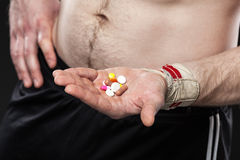 Young man holding a pill on black background. Stock Images