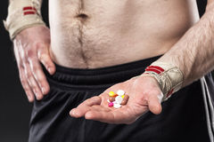 Young man holding a pill on black background. Royalty Free Stock Photos