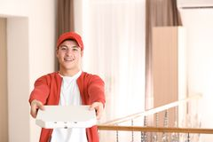 Young man holding pizza box indoors stock image