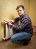 Young man holding pliers and installing radiator valve Royalty Free Stock Image