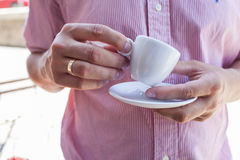 Young man holding porcelain cup with his morning espresso. Close Stock Images