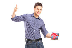 Young man holding a present and giving thumb up Stock Photos