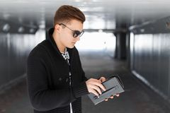 Young man holding a purse in his hands Stock Photos