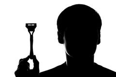 A young man holding a razor vertical - silhouette Royalty Free Stock Images
