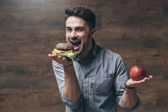 Young man holding red apple and biting tasty hamburger stock image