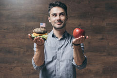 Young man holding red apple and delicious hamburger. Doubtful young man holding red apple and delicious hamburger Royalty Free Stock Images
