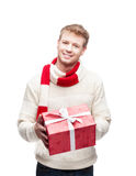 Young man holding red christmas gift. Young casual caucasian man holding red christmas gift with nice toothy smile Royalty Free Stock Image