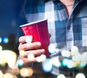 Young man holding red cup in a luxury party. Person having fun and drinking alcohol. Abstract and modern celebration concept Stock Image