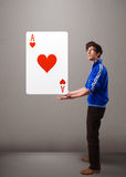 Young man holding a red heart ace Royalty Free Stock Image