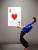 Young man holding a red heart ace Royalty Free Stock Photography