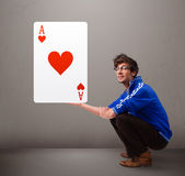 Young man holding a red heart ace Royalty Free Stock Photo