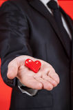 Young man holding a red heart on the palm Stock Photos