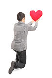 Young man holding a red heart rear view Stock Photography