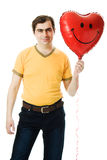 Young man holding a red heart shaped balloon Royalty Free Stock Photos