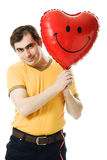 Young man holding a red heart shaped balloon Royalty Free Stock Images