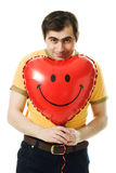 Young man holding a red heart shaped balloon Stock Photography