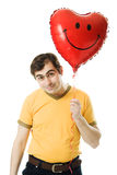 Young man holding a red heart shaped balloon Stock Images