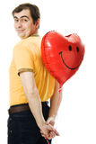 Young man holding a red heart shaped balloon Royalty Free Stock Image